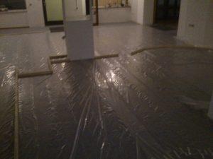 Boden ausgelegt mit Folie und Zuschnitt der ersten Tragelemente für die Trennwände