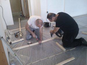 Josef und Rainer fixieren die erste Bodenleiste der ersten Trennwand