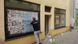 Feinarbeit bei der Beklebung der Fenster mit dem Computgeschichteposter