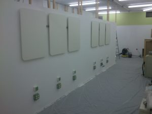 Eine Wand mit zwei mal drei Schildern und zugehörigen Steckdosen.
