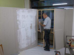 Josef befestigt die Platten für die Innenseite der ausstellugnsecke im Fenster