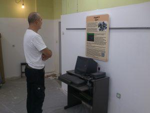Eine erste Tafel samt aufschrift an der Wand hinter einem Computer.