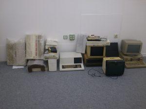 Eine Reihe von Rechnern aufgereiht an der Längswand der Ausstellung, bereit um in das Regal geräumt zu werden
