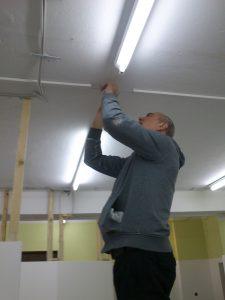 Josef steht auf der Leiter und befestigt die Deckel auf den Abzweigdosen.