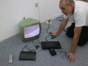 Josef kniet vor einem Fernseher mit angeschlossenem Sinclair Spectrum und schreibt ein kleines Testprogram