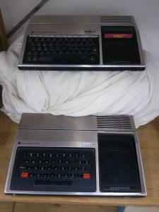 TI 99/4 und 99/4A im Regal, zusammen mit einer Erweiterungsbox die noch in einem Bettuch eingewickelt ist.