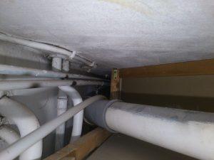 Innenaufnahme von der Zwischendecke im Flur. Viele Leitungen, Strom, Wasser und Heizung.