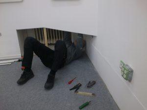 Josef liegt am Boden und verlegt die Kabel für die Ecke mit den Sinclair Rechnern.