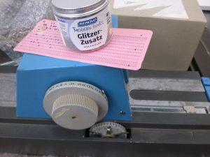 Eine Dose Glitzerzusatz für Wandfarbe auf einem Handstanzer für Lochkarten.
