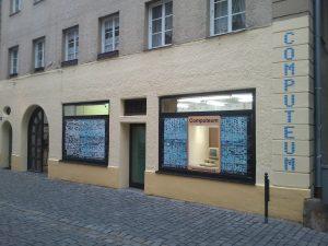 """Fassade des Computeum in der Abenddämmerung - jetzt mit Schriftzug """"Computeum"""" an der Ecke"""
